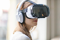 Woman wearing Virtual Reality Glasses and headphones - TAMF00771
