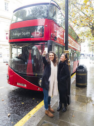 UK, London, two happy friends taking selfie with smartphone in front of red double-decker bus - AM05056