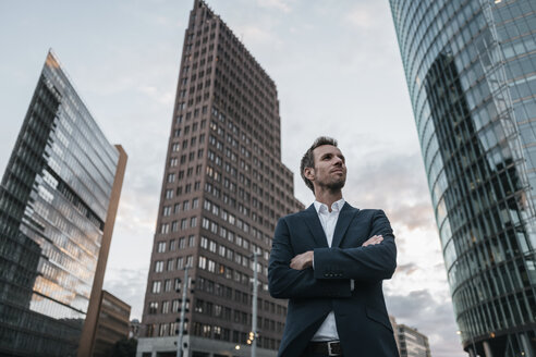 Germany, Berlin, businessman with arms crossed standing at Potsdamer Platz - KNSF00639