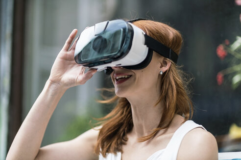 Redheaded woman wearing Virtual Reality Glasses - TAMF00781