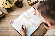 Young man planning journey using compasses - JRF01023