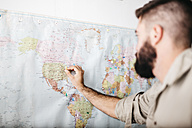 Young man selecting travel destinations on a world map - JRF01026