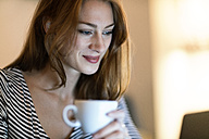 Portrait of smiling woman with cup of coffee using laptop - TAMF00784