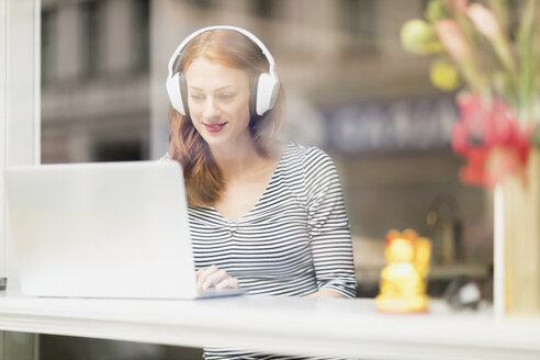Smiling woman sitting in a coffee shop using headphones and laptop - TAMF00787