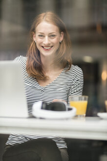 Portrait of happy woman sitting in a coffee shop - TAMF00790