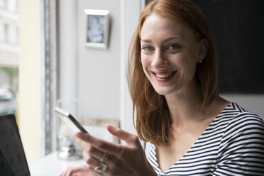 Portrait of redheaded woman with smartphone in a coffee shop - TAMF00793
