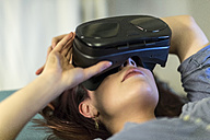 Young woman using Virtual Reality goggles - TAMF00796