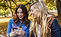 Two young women with smartphone in a park in autumn - MGOF02593