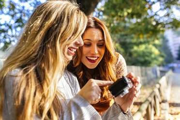 Two young women with camera in a park in autumn - MGOF02596