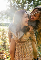 Two playful young women in a park in autumn - MGOF02599
