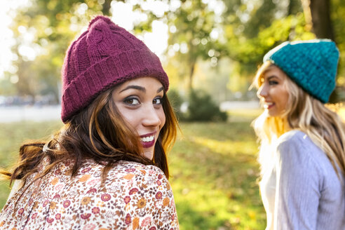Two young women wearing wooly hats in a park in autumn - MGOF02602