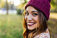 Portrait of smiling young woman wearing wooly hat - MGOF02605