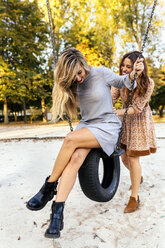 Two playful young women on a tire swing - MGOF02608