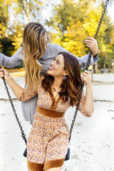 Two happy young women on a swing - MGOF02611