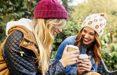 Two happy young women drinking coffee in a park in autumn - MGOF02614