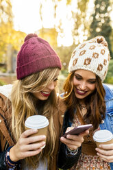Two young women with smartphone in a park in autumn - MGOF02617