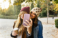 Two smiling young women taking a selfie in a park in autumn - MGOF02620