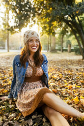 Smiling young woman in a park in autumn - MGOF02623