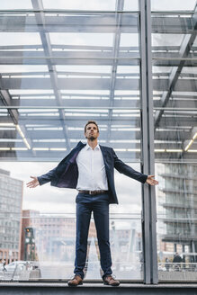 Businessman standing in front of glass pane - KNSF00665