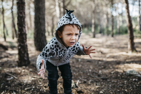 Portrait of little boy wearing hooded jacket playing monster in the woods - JRFF01044