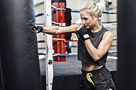 Female boxer exercising at punch bag - MADF01231