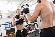 Female boxer sparring with coach - MADF01255