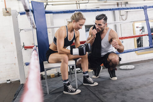 Coach talking to female boxer in boxing ring - MADF01264