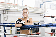 Portrait of confident female boxer in boxing ring - MADF01270