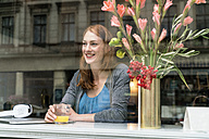 Portrait of happy woman sitting in a coffee shop looking through window - TAMF00810