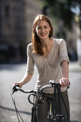 Portrait of redheaded woman with bicycle - TAMF00822