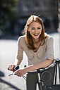 Portrait of redheaded woman with bicycle - TAMF00825