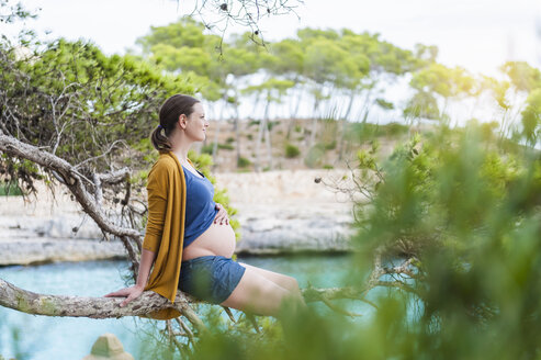 Pregnant woman sitting on branch at the sea - DIGF01438
