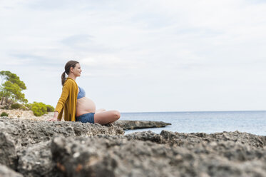 Pregnant woman sitting on rock at the sea - DIGF01447