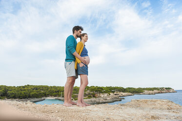 Expectant parents standing at the sea - DIGF01450