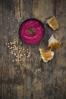Bowl of beetroot hummus, chick-peas and flat bread on dark wood - LVF05581