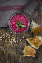 Glass of beetroot hummus, chick-peas and flat bread on dark wood - LVF05584