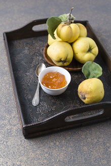 Wooden bowl of quinces and bowl of quince jelly on tray - MYF01852