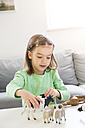 Little girl playing with animal figurines at home - LVF05591