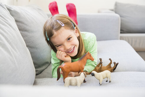 Portrait of smiling little girl lying on couch with her animal figurines - LVF05594
