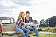 Couple sitting on pick up truck reading map - FMKF03186