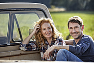 Couple sitting on pick up truck - FMKF03216