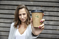Young woman holding takeaway coffee cup with smiley face - FMKF03225