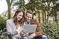 Smiling young couple using tablet in park - FMKF03228