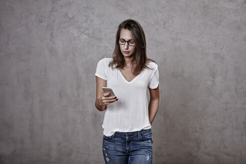 Young woman looking on cell phone - FMKF03243