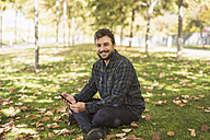 Portrait of smiling man with smartphone sitting on meadow in autumn - JASF01288
