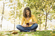 Woman sitting on meadow in autumn looking at cell phone - JASF01291