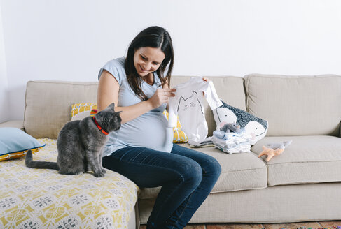 Pregnant woman with cat sitting on couch, looking at baby sleepers - GEMF01241