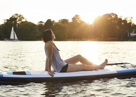 Germany, Hamburg, Young woman on paddleboard enjoying summer - WHF00038