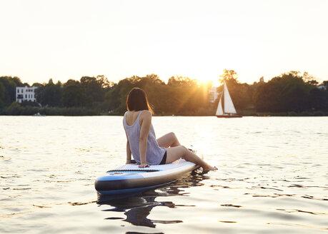 Germany, Hamburg, Young woman on paddleboard enjoying summer - WHF00044