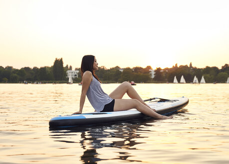 Germany, Hamburg, Young woman on paddleboard enjoying summer - WHF00047